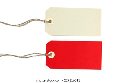 Two blank gift tags in creme and red color with natural string - isolated on white background