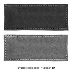 two blank gray  leather labels of different tint on white background