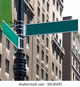 Two blank green street signs on a post at the intersection of two city streets. Insert your own words to easily customize the message.