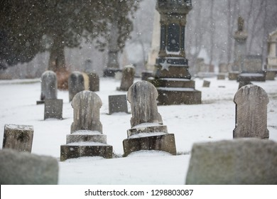 Two Blank Headstones in Cemetery with Snow Falling in Winter