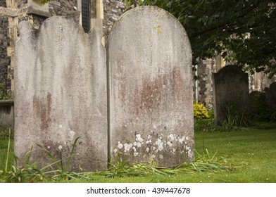Two blank headstones in the graveyard of Buckland Church of St Andrew, Dover, England, UK. Wilted daffodils and grass surround the weathered stones.