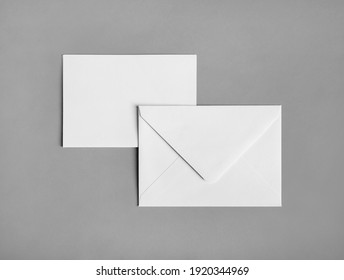 Two blank paper envelopes on gray paper background. Back and front. Flat lay.