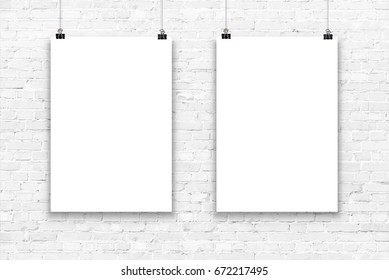 Two blank paper poster mockup on a white brick wall.