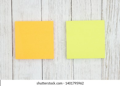 Two blank sticky notes on weathered whitewash textured wood background you can use as a mockup for your message