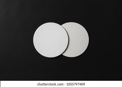 Two blank white beer coasters on black paper background. Responsive design mockup. Flat lay.