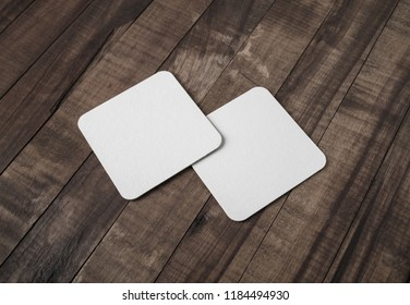 Two blank white beer coasters on vintage wooden background. Responsive design mockup.