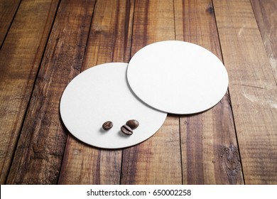 Two blank white beer coasters and coffee beans on vintage wooden table background.