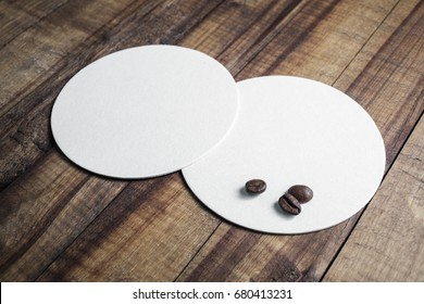 Two blank white beer coasters and coffee beans on wooden table background. Responsive design mockup.