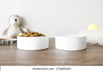 Two blank white ceramic pet bowls on wood floor with pet accessories, water and food pet bowls mockup