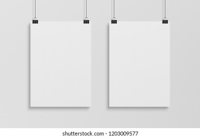 Two blank white poster hanging up with in front of white wall clips mockup