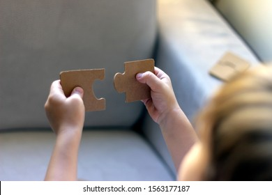 Two blank white puzzle pieces in boys hands.Little boy is trying to connect couple jigsaw puzzle piece.Boys holding in hands two puzzle pieces up in the air,trying to put them together.Copy space.