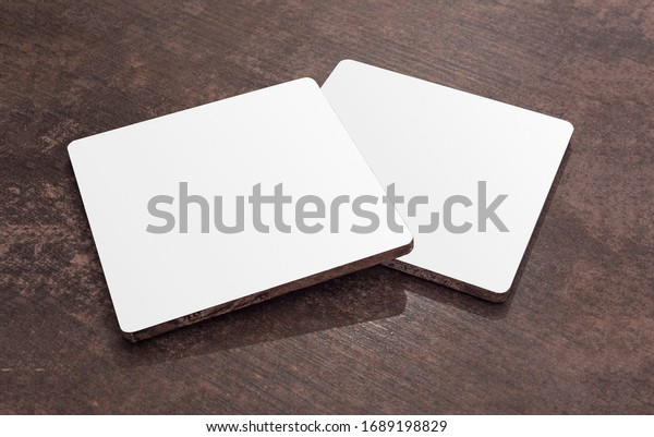 Two blank white quadratic drink coasters lying on the wooden table. Mock up. Clean square can mat isolated on a wooden table.