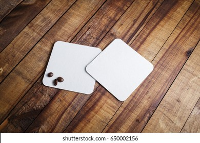 Two blank white square beer coasters and coffee beans on wooden table background.