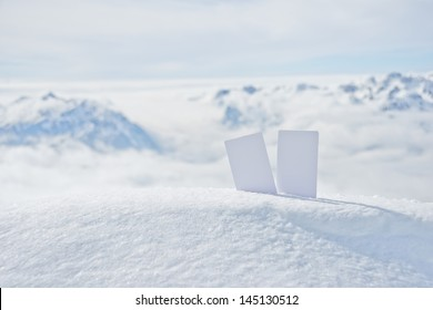 Two blank winter sport ski pass tickets on mountain top. Concept to illustrate winter sport admission fee