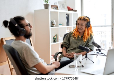 Two bloggers, young man and woman in headphones looking at each other while talking, recording conversation, interview for video blog. Content creator, filming, blogging. Horizontal shot