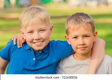 Two blond boys in white and blue T-shirts standing embracing in summer park