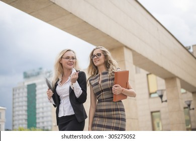 Two blond businesswoman walking on the street near office building Couple of business woman going together with paper documents and tablet computer against blue summer sky with clouds Fast move