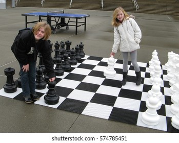 Two blond girls playing chess on a large chess board outdoors