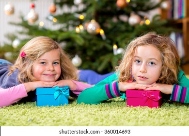 two blond girls with presents in front of christmas tree