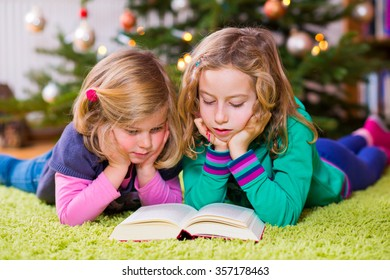 two blond girls reading a book  in front of christmas tree