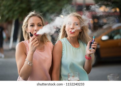 two blond sisters smoking from vaporizer pipe
