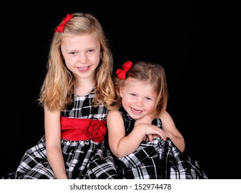 Two blond sisters studio portrait isolated on black