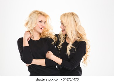 Two blonde beautiful sisters twins looking at each other and smiling over white background