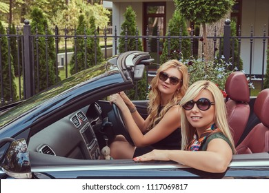 Two blonde female friends wearing fashionable clothes in sunglasses sitting in a cabriolet car on a summer trip vacation.