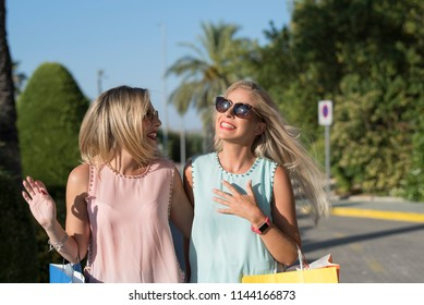 Two blonde woman sister smiling and laughing happy after shopping