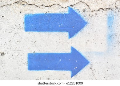 Two blue arrows spray-painted on the white wall
