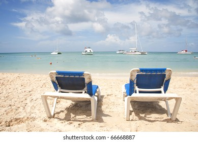 Two blue beach chairs on a tropical beach overlooking the ocean.