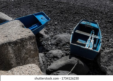 Two blue boats on the rocks on a beach on the island of Madeira