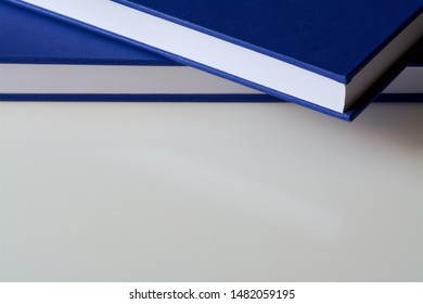 Two blue bound books with white pages and copy space below. Could be copies of a dissertation/thesis, academic journal or encyclopedias.