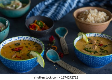 Two blue bowls of Asian soup on a table with condiments and peppers