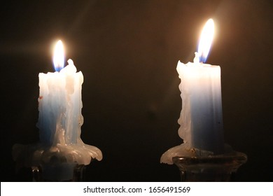 Two blue candles with drips of paraffin burn in the dark