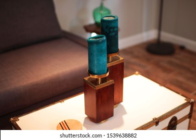 two blue candles on a white coffee table next to a brown sofa in a well lit living room