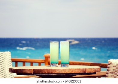 Two blue cocktails on the summer beach terrace of the restaurant on the background of the sea, the ocean