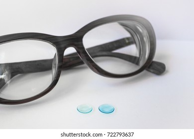 2743004f255 Two blue contact lenses and modern female glasses. The dark frame lies  diagonally. Daylight