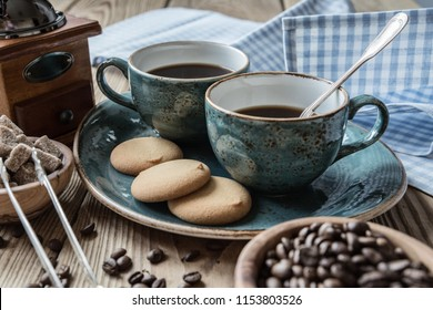 Two blue cups of black coffee, cookies and sugar pieces surrounded by checkered linen cloth and coffee beans on old wooden table