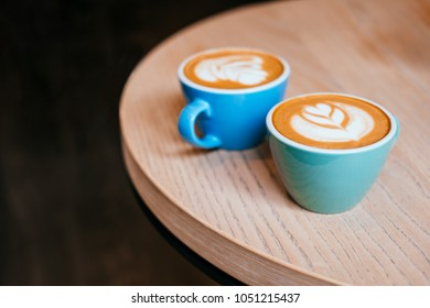 Two blue cups of cappuccino with beautiful latte art on the table.