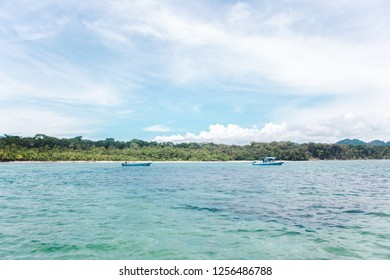 Two blue fishing boats off the jungley Caribbean coast of Cahuita, Costa Rica