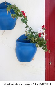 Two blue flower planters hanging on a white stone house facade on the mediterranean island Bozcaada in Turkey.