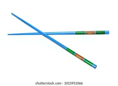 Two blue japanese chopsticks (hashi - jap.) crossed on white background.