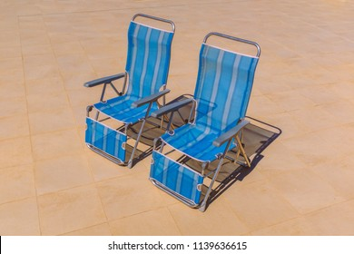 Two blue nylon stripe foldable  recliner deck chairs in an upright position with no body sitting on them. They are on a stone patio in bright sunshine with a dark shadow of the chairs