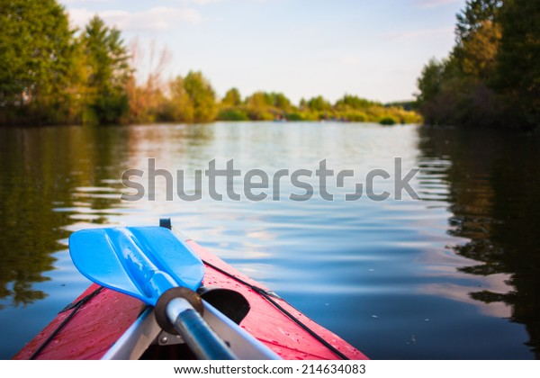 Two blue paddles are lying on kayak. Kayaking on a river.