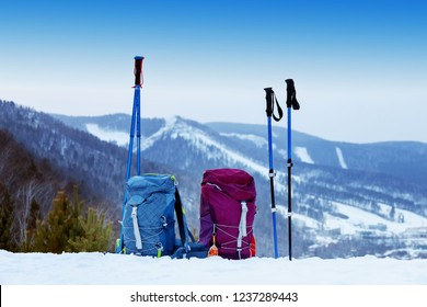 two blue and pink backpacks with walking sticks on the background of snow-capped mountains in the winter, the concept of romance and family walks in the hike