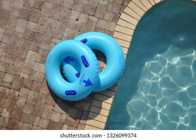 Two blue pool floats by the edge of the swimming pool.