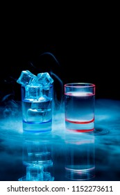 Two, blue and red shot glasses full of drinks one of wich with ice in a theatrical smoke on a black background. Conceptual, commercial and advertising photo. Copy space.