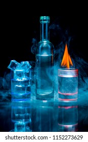 Two, blue and red shot glasses full of drinks one of wich with ice and second is burning, and a bottle in a smoke on a black background. Conceptual, commercial and advertising photo. Copy space.