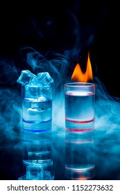 Two, blue and red shot glasses full of drinks one of wich with ice and second is burning in a thratrical smoke on a black background. Conceptual, commercial and advertising photo. Copy space.